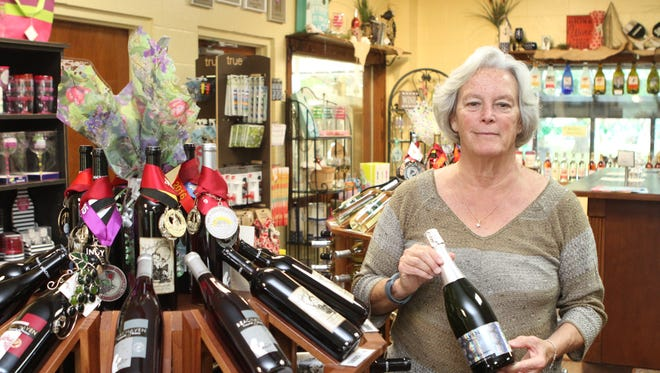 Beachaven Vineyards & Winery's Louisa Cooke holds a bottle of 30th anniversary champagne. Cooke's father, Judge William O. Beach's love for champagne led to the creation of Clarksville's beloved winery. .