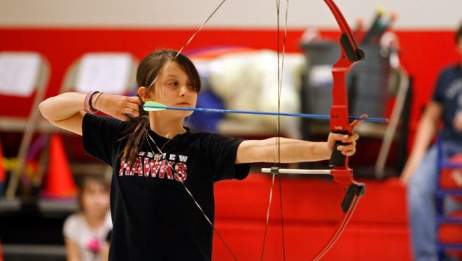 A student tries her hand at archery, one of the sports that will be taught and demonstrated at Sportsfest.