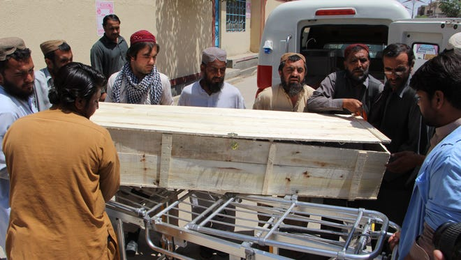 People shift a coffin containing a body of one of the two people who died in a US drone strike that killed Taliban leader Mullah Akhtar Mansoor, after the bodies were brought to a hospital in Quetta, Pakistan, on May 22, 2016.
