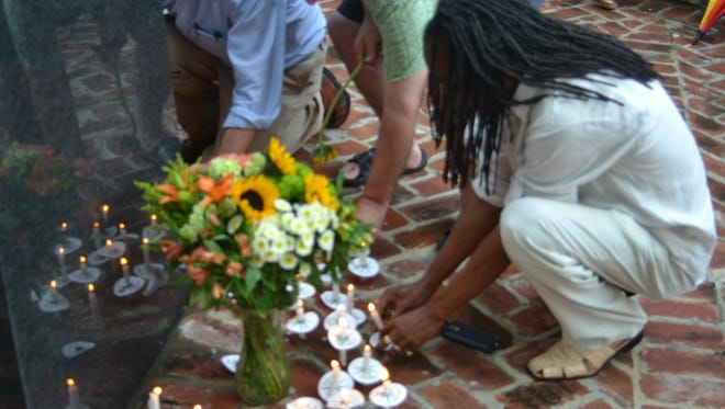 Participants place candles at the Alexandria Holocaust Memorial during a ceremony Monday night to remember the victims of the recent mass shooting in Orlando, Florida.