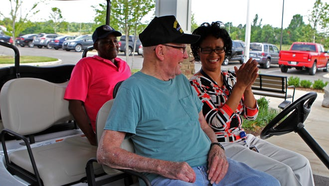 Tennessee State Veterans Home Activity Director, Lisa Hunt, right, takes resident Homer Salyer, center, and Desert Storm Veteran Tommy Jurnett for a ride Thursday in a golf cart donated by AMVETS.