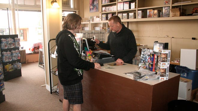 Nicholas Coffey helps a customer at  Astonishing Adventures & Collectibles,  101 S. First Street in Silverton.