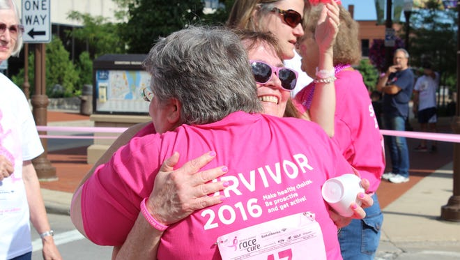 Volunteer Suzy Klimek, foreground, hugs a breast cancer survivor at the finish line of the Komen Central Wisconsin Race for the Cure in downtown Wausau on Aug. 14, 2016.