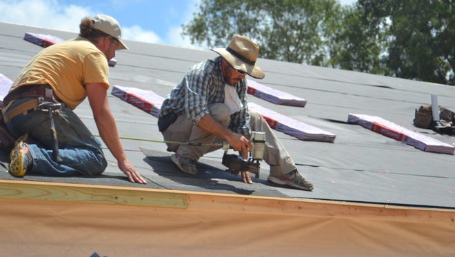 Volunteers lay down roof shingles at the new Hornbeck United Pentecostal Church.
