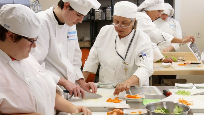 From right, Ada DeCecco instructs students about the proper way to slice carrots and celery at Tilly Foster Educational Center.