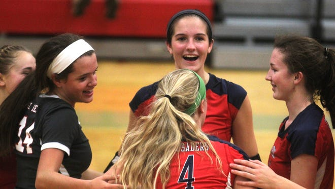 St. Henry sophomore Maria Tobergte, facing, and teammates celebrate the end of their victory.  St. Henry 3, Beechwood 0. KHSAA 9th Region volleyball semifinals. Dixie Heights HS Edgewood KY.