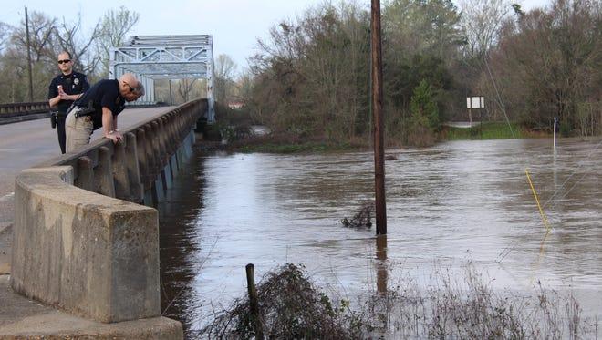 Petal law enforcement officials Matthew Hiatt, Josh Barham and Mike Trest observe the Leaf River in March after heavy flooding.
