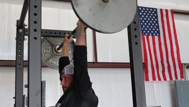 Jason Lyon lifts weight behind an American flag from Operation Enduring Freedom. The strength trainer says it's one of his most prized gifts.