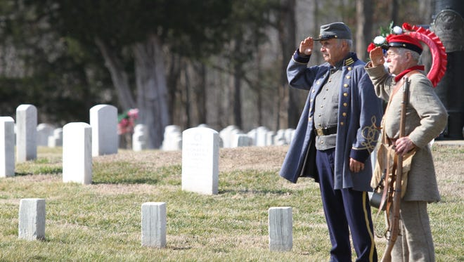 Bob Falkner and George Wallace salute the flag at a Fort Donelson ceremony honoring fallen Federal and Confederate soldiers who died in the Battle of Fort Donelson.