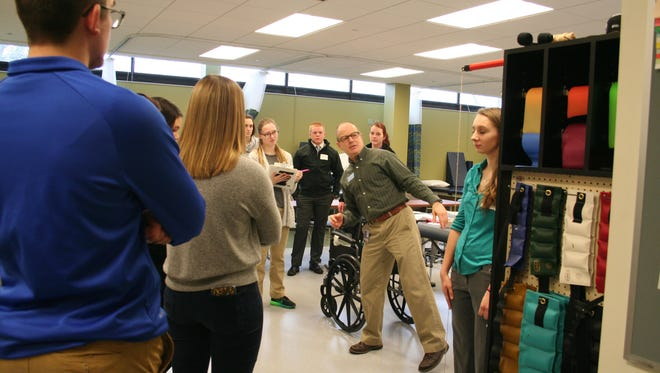 Bruce Wassung, physical therapist assistant chair and director of clinical education, runs the students through a spine alignment evaluation process using a plumb bob.