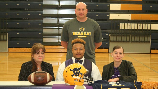 Battle Creek Central standout Carlos Parks has committed to play football at Albion College. He is joined by his family and BCC coach Lorin Granger.