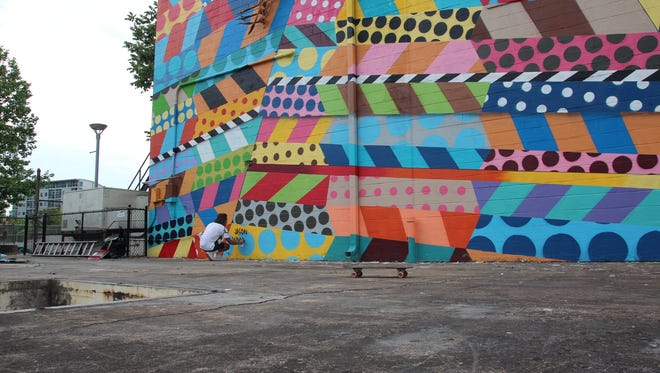 Artist Jason Woodside working on his mural in the Gulch.