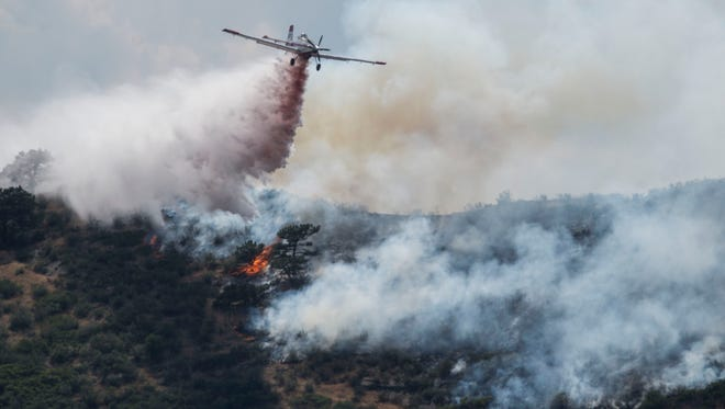 An airplane drops fire retardant on a wildfire burning between Loveland and Fort Collins at the Coyote Ridge Natural Area, Saturday, July 22, 2017, just south of Fort Collins, Colo.
