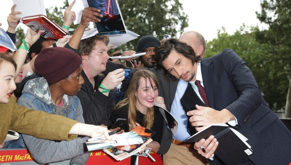Adam Driver pauses for selfies with fans.