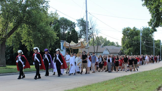 Lourdes Academy students and staff take part in a eucharistic procession in this file photo.