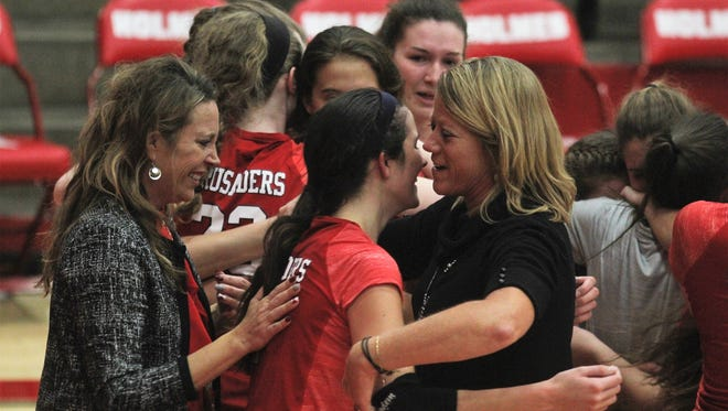 St. Henry coaches Shawn Schwarz, left, and head coach Maureen Kaiser celebrate with junior Maria Tobergte during St. Henry's 3-2 win over Notre Dame in the Ninth Region volleyball championship Oct. 26, 2017 at Holmes HS, Covington.