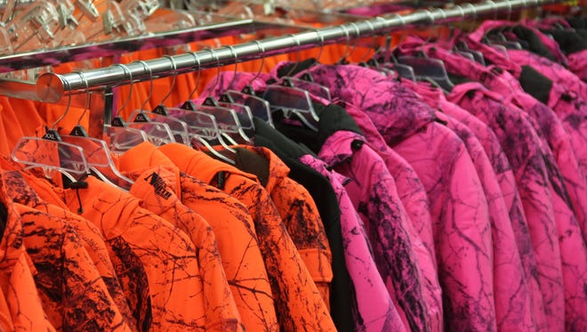 Blaze pink and blaze orange hunting coats hang from a rack in Wisconsin. Thanks to the work of two novice hunters — young sisters from the Eastern Shore — Maryland hunters may soon be allowed to wear bright pink safety gear.