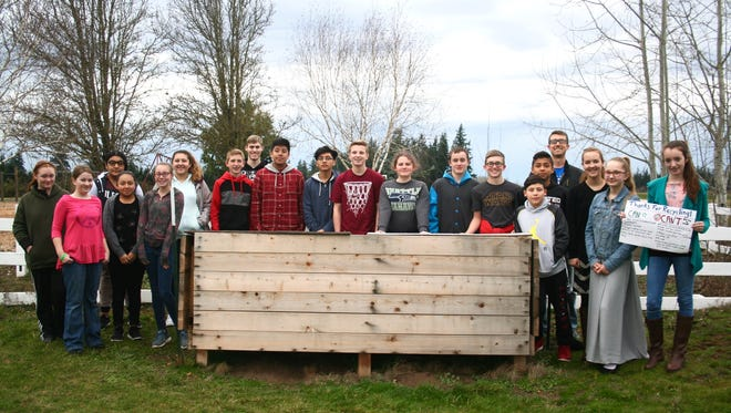 Butte Creek's leadership class surrounding their composting bin near the school garden. Garron Lamoreau is at the back right, while high school assistant Tyler Bishop as at the back left.