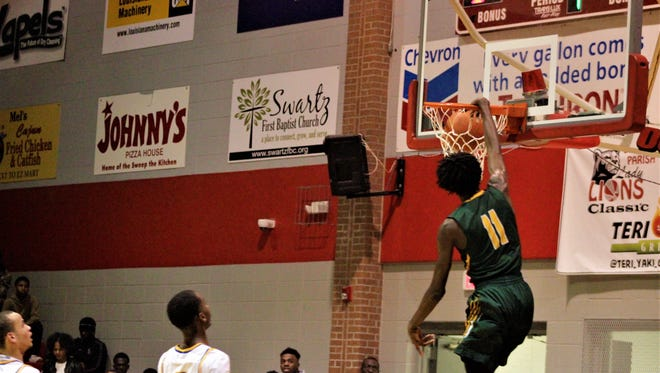 Rayville senior forward Nashaun Ellis (11) slams one home in the Hornets' victory over the East Ascension Spartans in the championship game of the 2018 Don Redden Memorial Classic at Ouachita Parish High School's Madhouse on Millhaven.