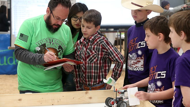 A contest judge talks with a team who participated in the third junior robotics competition at the San Angelo Stock Show and Rodeo on Friday, Feb. 2, 2018.