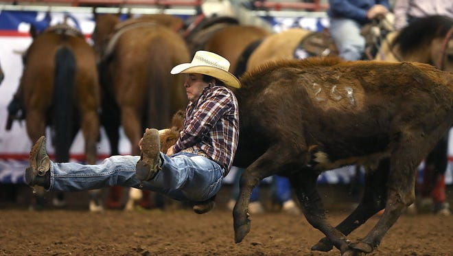 Mason Miles Carter of Checotah, Oklahoma, competes in steer wrestling on Day 1 of slack Monday inside the Foster Communications Coliseum.