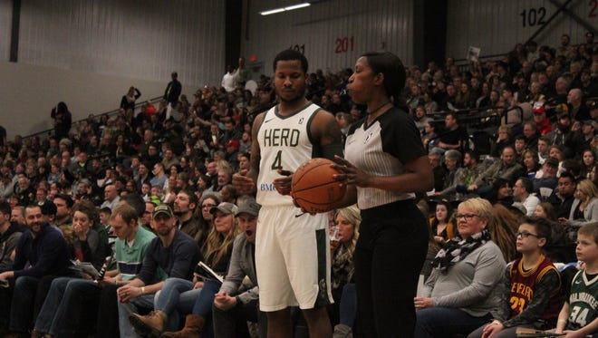 NBA G League official Shante Anderson hands the ball to the Wisconsin Herd's Jarvis Summers during a recent game at Menominee Nation Arena.