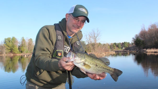 Jason Halfen of Eau Claire prepares to release a largemouth bass caught on the Chetek Chain on opening day of the 2018 Wisconsin fishing season.