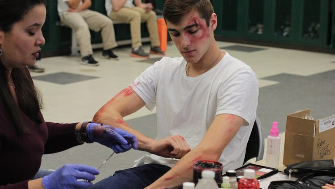 Saint Joseph High School junior, Luke Fresco, pretended to be paralyzed in a mock crash exercise at the school. and the jaws of life had to be used to remove him; he is shown here getting make up.