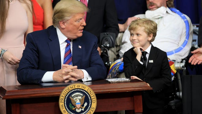 President Donald Trump signed the right to try bill Wednesday allowing terminally ill patients to use experimental medicines that have not yet been approved by the Food and Drug Administration. Eight-year-old  Jordan McLinn of Indianapolis watches. McLinn Duchenne muscular dystrophy, which weakens muscles and is fatal.