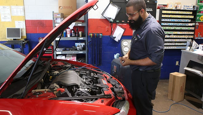 Mechanic Ross Spear-Martinez with Firestone Complete Auto Care surveys a car brought in for repairs on Labor Day Monday, Sept. 3, 2018.