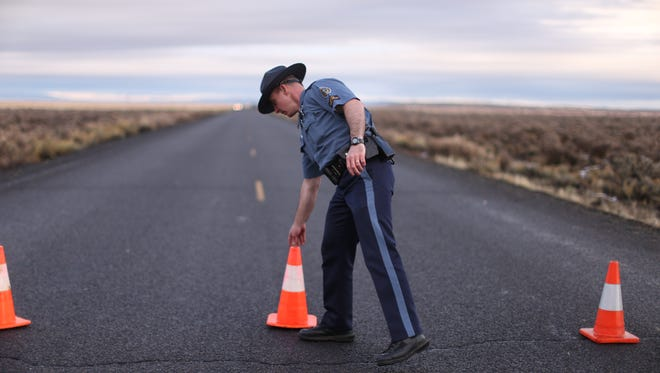 An officer with the Oregon State Police moves a cone to establish a roadblock along one of the routes to the Malheur National Wildlife Refuge in Harney County, Ore., on Jan. 28, 2016.