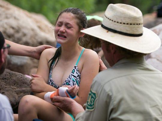 River Ranger Mike Roseman treats Cheyenne Moody, 11,