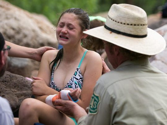 River Ranger Mike Roseman treats Cheyenne Moody, 11, after she broke her arm at Fossil Springs on Friday, June 12, 2015.