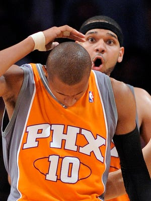 Phoenix Suns Leandro Barbosa, left, of Brazil holds his head as teammate Jared Dudley looks on after he was injured from sliding into photographers during the second half of Game 2 of the NBA basketball Western Conference finals, Wednesday, May 19, 2010, in Los Angeles. Dudley and Barbosa are once again teammates in Phoenix.