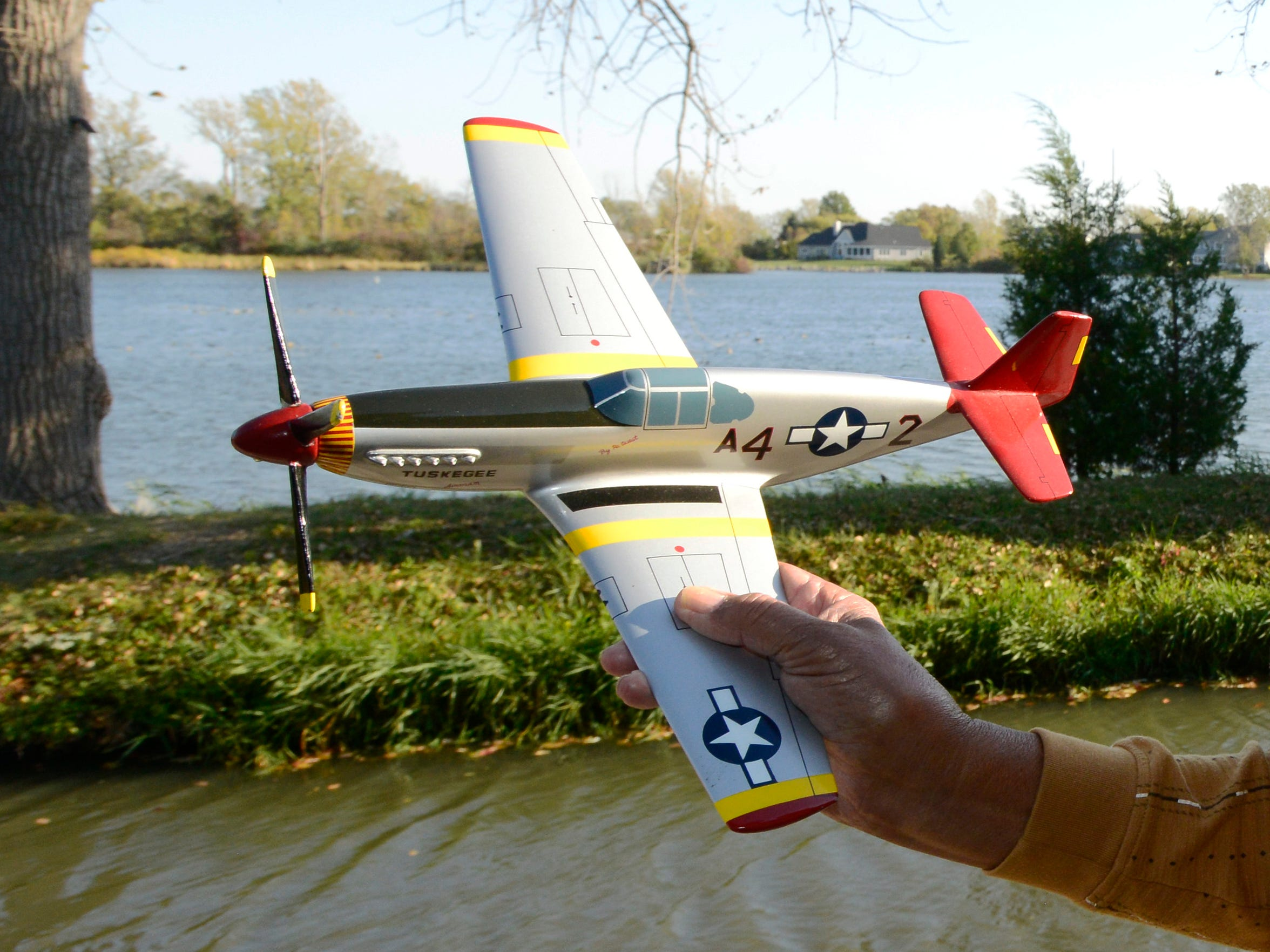 Harold H. Brown holds a model of the P-51 C Mustang,