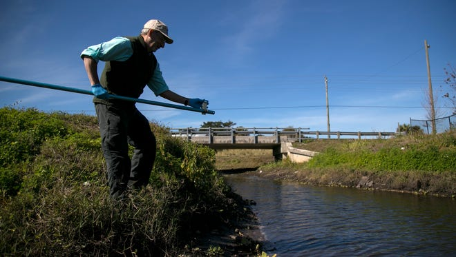 John Cassani gets a sample of the water at Billy's Creek in Fort Myers on Wednesday, Jan. 31, 2018. The waterway has tested high for contaminants.