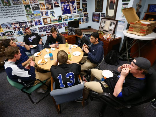 Metuchen and Middlesex high schools conduct share pizza for lunch in the Atletic Director's office during an 'Athlete Exchange' involving five baseball players from each school, the players spending the school day together at Metuchen High School. The  program is designed to build camaraderie and to instill mutual respect between the sports programs at both schools. April 17, 2018. Metuchen, NJ.