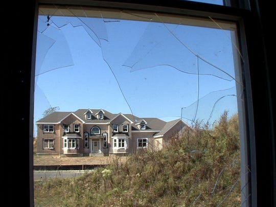 A home under construction by Kara Homes is shown through broken glass of another home in the Hawkin Ridge development off Hawkin Road in Jackson Township in 2007.
