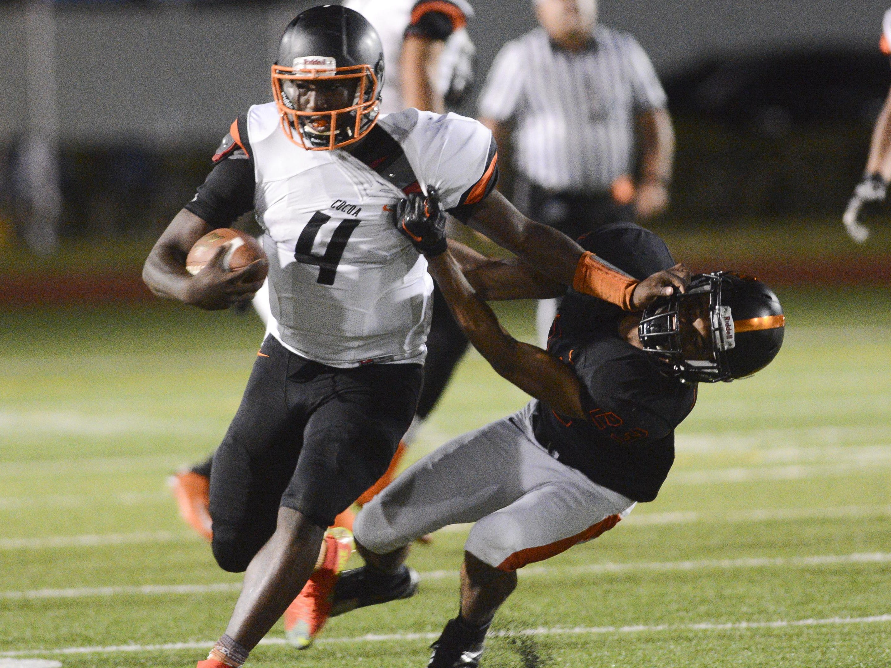 Cocoa QB Bruce Judson (4) tries to fend off Marquis Decius of Booker T. Washington (23) during Friday's game in Miami