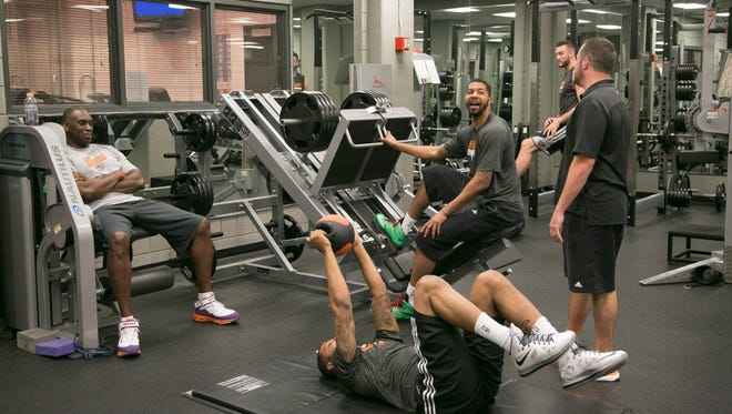 Suns' Mark West (L) and trainers watch over Marcus Morris (center), Markieff Morris and Miles Plumlee (back) as they workout in the offseason at US Airways Center in Phoenix on Friday, July 25, 2014.