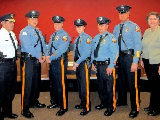 Pompton Lakes Police Chief Moises Agosto helps swear