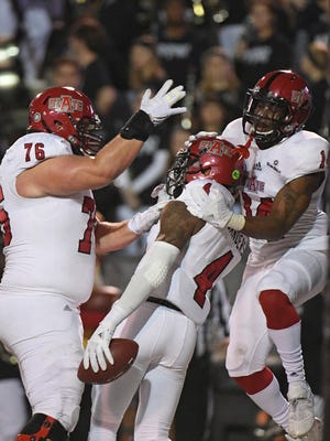 Arkansas State's Austin Moreton (76) and Chris Murray (14) celebrate with wide receiver Kendall Sanders (4) after Sanders' touchdown catch during the first half of an NCAA college football game against Troy in Troy, Ala., Thursday, Nov. 17, 2016. (Thomas Graning/Troy Messenger via AP)