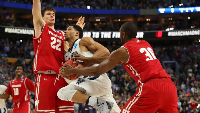 Villanova guard Josh Hart drives to the basket against Wisconsin forwards Ethan Happ, left,  and Vitto Brown with three seconds remaining in their NCAA Tournament game last Saturday.