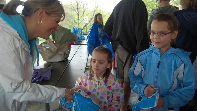 Fort Mitchell Recreation Director Kim Stoll hands bags of Easter eggs to Madison Wells, 5, and her sister Hannah, 9, of Fort Mitchell at the annual Easter egg hunt in 2011. The hunt was held at General Ormsby Mitchel Park.