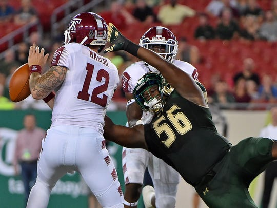 Temple Owls quarterback Logan Marchi (12) scrambles under pressure from South Florida Bulls defensive end Juwuan Brown (56) during the first half at Raymond James Stadium.