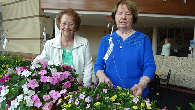 Bev Ruehle, left, and Gennie Rios, sell flowers Friday as a benefit for the Women's Auxiliary for the Bucyrus Community Hospital.