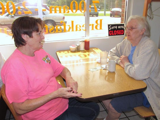 Honey B's Cafe owner Winnie Bennett, left, chats with regular customer Betty Rush of Millport.