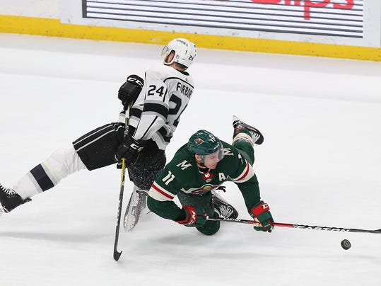 Minnesota Wild's Zach Parise (11) and Los Angeles Kings Derek Forbort (24) fall while going after the puck in the first period of an NHL hockey game Monday, March 19, 2018, in St. Paul, Minn. (AP Photo/Stacy Bengs)