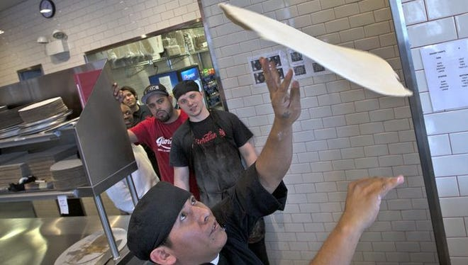 Raul Macedo gets an audience as he throws dough for a pizza crust, at Giordano's, Tuesday, Jan. 27, 2015.