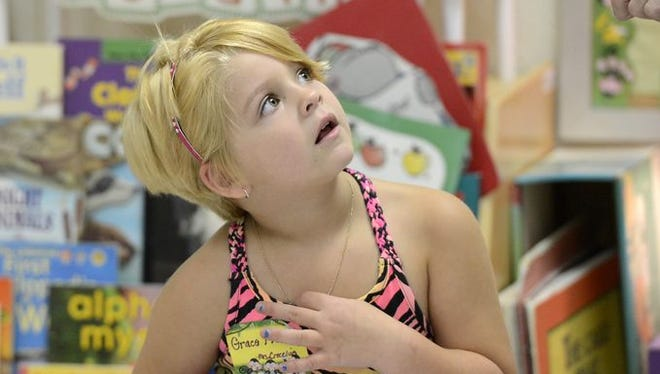 Grace Fleming listens to Mountain Home Kindergarten teacher Kim Crecelius during the first day of classes last August.